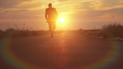 stock-footage-man-in-suit-business-running-road-sunset-path-lens-flare-hd